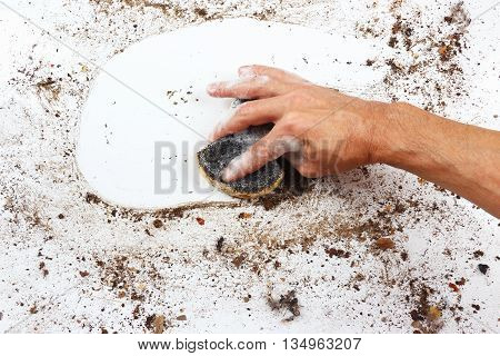 Hand with wet sponge cleans a heavily dirty surface