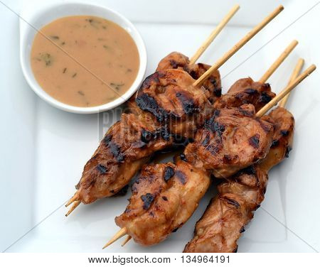 Chicken Satay on a skewer with grill marks; shown on a white plate with peanut dipping sauce on the side. Closeup from above.