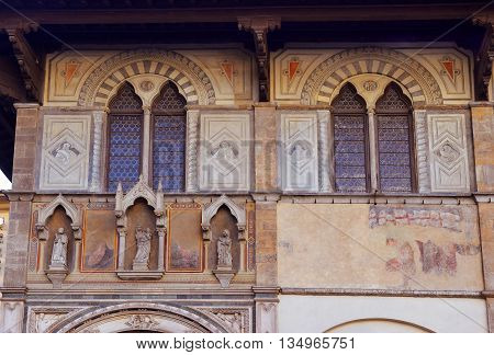 facade of medieval palazzo, decorated with frescoes and sculptures in Florence, Italy