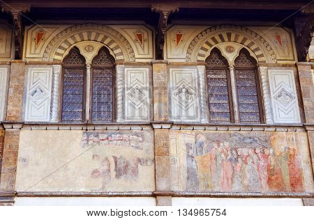 facade of medieval palazzo, decorated with frescoes and paintings in Florence, Italy
