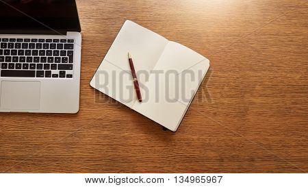 Top view shot of diary with pen and a laptop on wooden table.