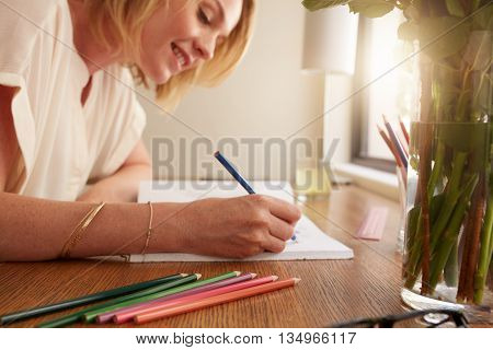 Woman Coloring An Adult Coloring Book With Pencils