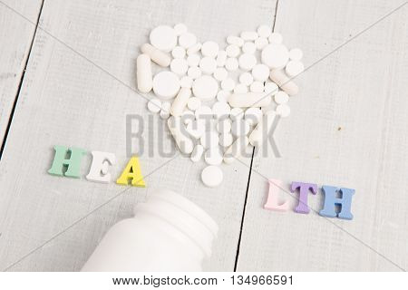 Medical Concept - Color Health  Inscription And White Heart Of Pills And Capsules