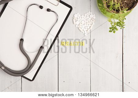 Medical Concept - Stethoscope, Pad, Bottle, White Heart Of Pills And Capsules, Health Inscription