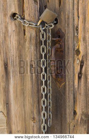 old wooden door with iron handle padlock chain - fragment