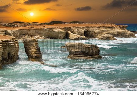 fantastic seascape - turquoise sea with waves and rocks on the background of orange sunset. Cliffs at water. Mediterranean coast near Paphos Cyprus