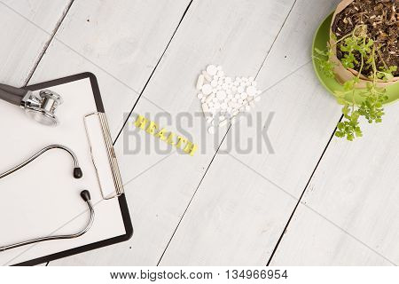 Medical Concept - Stethoscope, Pad, White Heart Of Pills And Capsules, Health Inscription