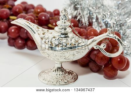 Silver Aladdin's magic lamp and red grapes. Ramadan Eid concept background