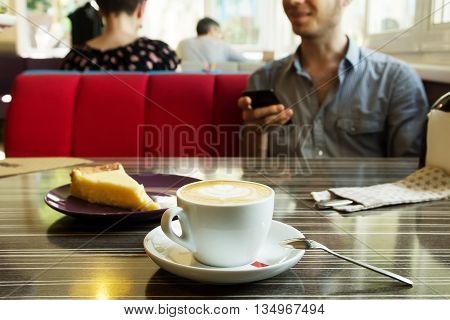 Morning cappuccino coffee and cheesecake. Cheesecake and kitchen appliances on the background. Coffee with art foam. Guy with the phone drinks cofee.
