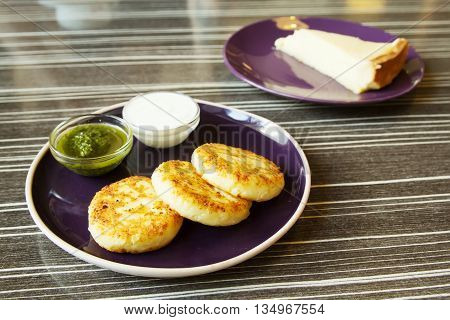 Homemade Salty Cheese Pancakes with sauce Pesto. Cheesecake dessert on the background. Pancakes photographed close.