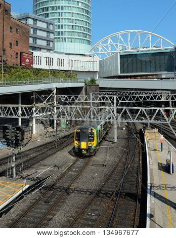 BIRMINGHAM, UNITED KINGDOM - JUNE 6, 2016 - Train arriving at New Street railway station with the Bullring to the rear Birmingham England UK Western Europe, June 6, 2016.