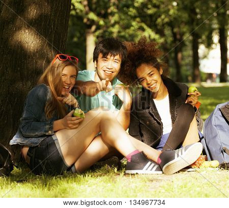 cute group of teenages at the building of university with books huggings, diversity nations, having lunch