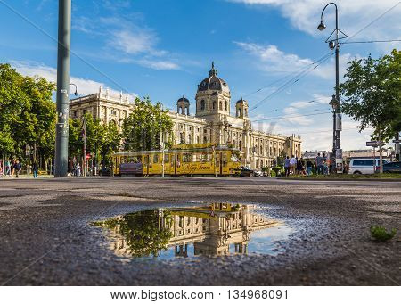 VIENNA AUSTRIA - 12TH JUNE 2016: The outside of the KH Museum in Vienna and a Yellow Ring Tram. Reflections can be seen in a puddle. People can be sen in the distance.