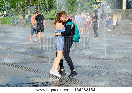MOSCOW, RUSSIA - May 26, 2016: Boy and girl bathing in city fountain. Hot summer heat. Girls in wet summer dress. Young man hugs girl. Icy freshness, happiness, love, affection.