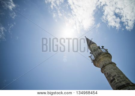 Image of a minaret against a sunny sky.