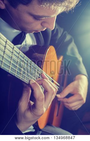 Guitarist. Man playing guitar on a black background