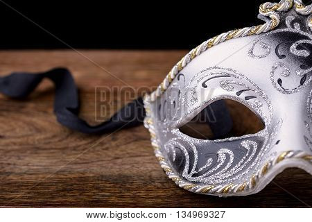 mask carnival white, black and gold on wood on a black background