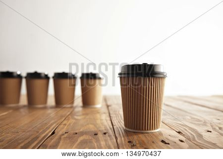 One focused cardboard paper coffee cup with black cap isolated on side in front of unfocused four take away cups on brushed vintage wooden table
