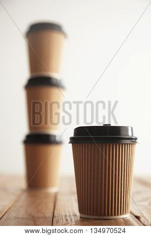 One focused cardboard paper cup in front of three take away cups with black caps standing in column on rustic vintage table isolated on white