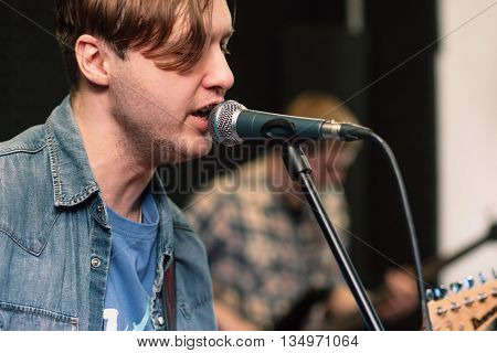 Guy singing into the microphone close-up. Profile of emotionally singing man on stage, guitar player on blurred background. Vocalist in jeans coat with closed eyes sings.