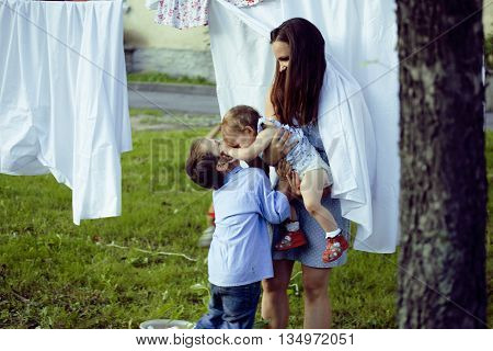 mother with her children outside hanging laundry, brother playing with little sister, happy loving family at summer, lifestyle people concept