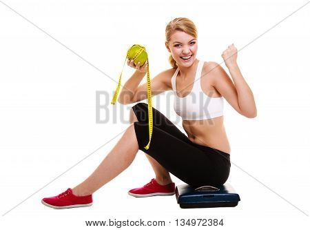 Woman sitting on weighing scale holding grapefruit and measurement tape raises raising her arms. Successful diet dieting slimming. Healthy lifestyle and body care concept.