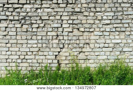 Background of old cracked white brick wall with green grass