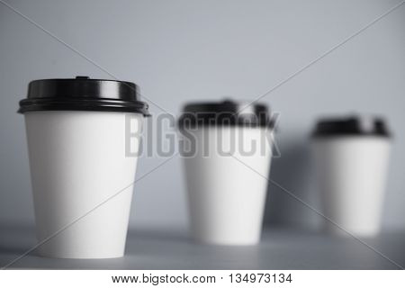Three take away white paper cups with closed black caps, top view, isolated on simple gray background, left cup in close focus, cups behind are unfocused in bokeh
