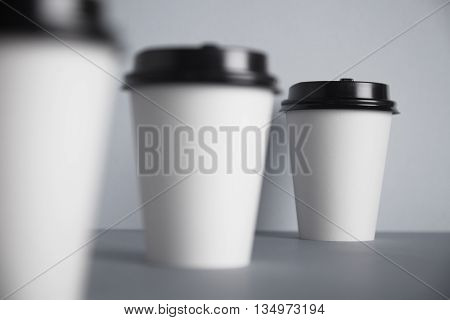 Three take away white paper cups with closed black caps, top view, isolated on simple gray background, last cup in close focus, cups ahead are unfocused in bokeh