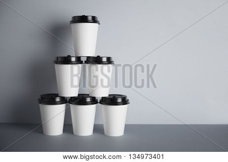 Pyramid made from six white take away paper cups with closed black caps, isolated on simple gray background on side