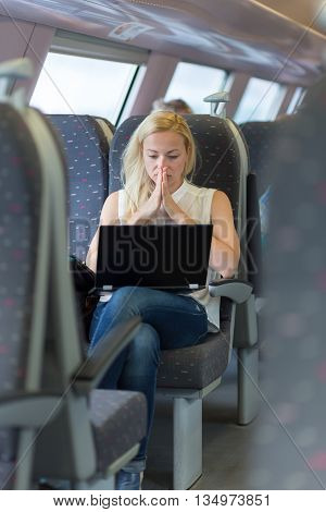 Businesswoman sitting and traveling by train working on laptop.