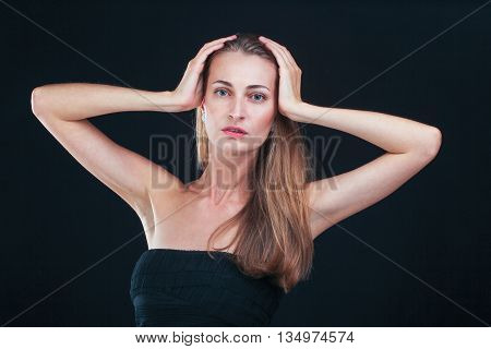 Awful headache. Pretty woman holding head in hands standing against black background