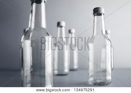 Close view on clear unlabeled empty glass bottles for cold beverages and drinks, randomly presented and isolated on gray background