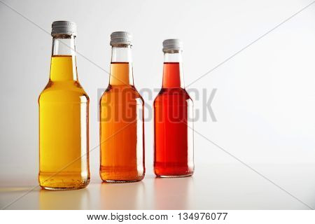 Three glass bottless with colored drinks inside: red, orange, yellow. Presented on white table, isolated on white. Ready for labeling and sale
