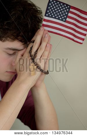 Teenage boy praying with a rosary and American Flag