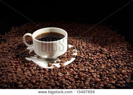 grãos de café com copo branco