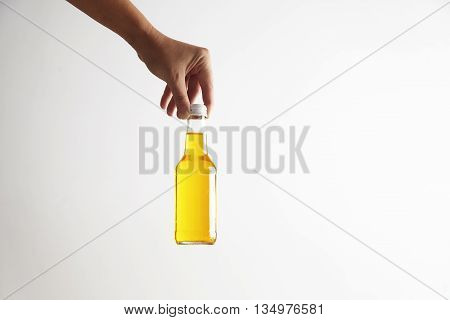 Hand puts down closed rustic glass bottle with tasty cold drink inside, isolated on white in center