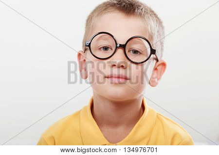 Portrait close up of cute serious kid little boy nerd in glasses.