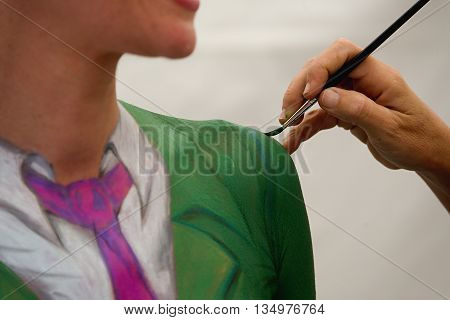 Body painting in process.Young female nude body art painter