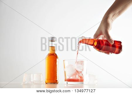 Hand pours berry cider drink into glass with ice cubes near sealed closed unlabeled bottle with orange aperol