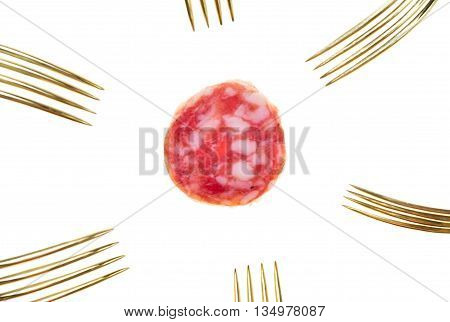 a slice of salami sausage and many vintage silver and golden forks