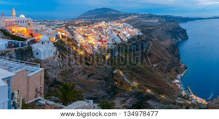 Fira, main town of the island Santorini, sea, white houses and church during twilight blue hour, Greece