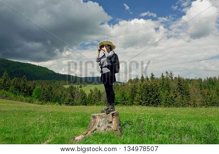 Young tourist woman standing on a tree stump with a camera in hand making photo pictures of the beautiful landscape with green trees and storm clouds