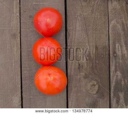 Fresh, ripe tomatoes on the dark wood background, copy space.