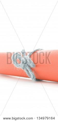 Handmade natural string knot tied on orange letter tube, isolated