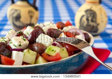 Close up of greek salad with feta cheese tomatoes cucumber olives and onions with greek amphorae over a red napkin