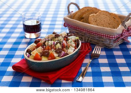 Greek salad with feta cheese olives tomatoes cucumber and onions over a checkered tablecloth with red wine and bread