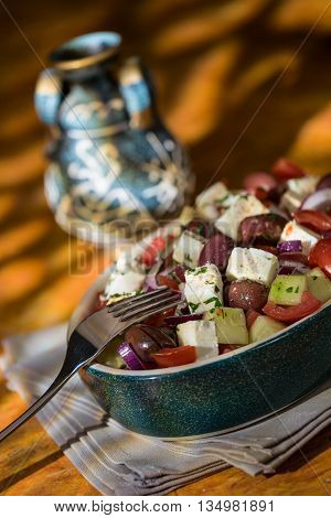 Greek salad with feta cheese tomatoes cucumber olives and onions with greek amphora over a grey napkin