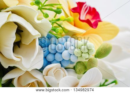 Beautiful handmade art clay spring flower bouquet. Bridal accessory. Over white background.