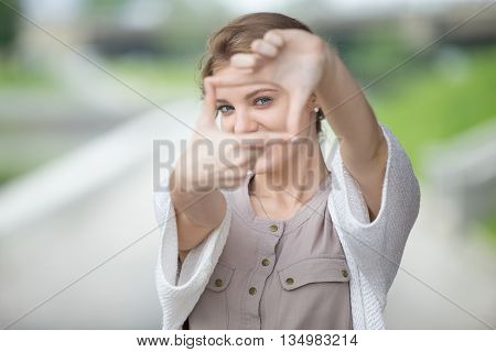 Portrait Of Playful Woman Using Hands To Make A Frame